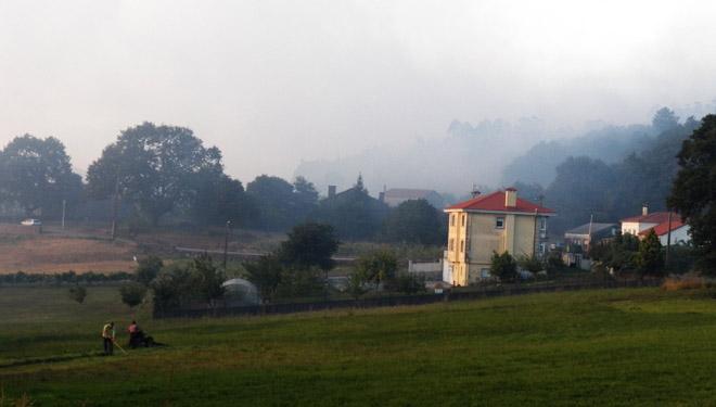 Dous veciños segan un prado a tarde do xoves. Ao fondo, o lume chegaba a súa fin.