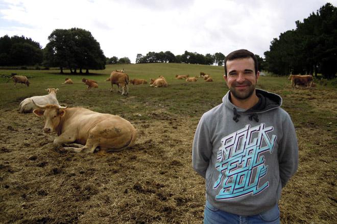Ángel Santos, xunto ás súas vacas nun prado preto da casa