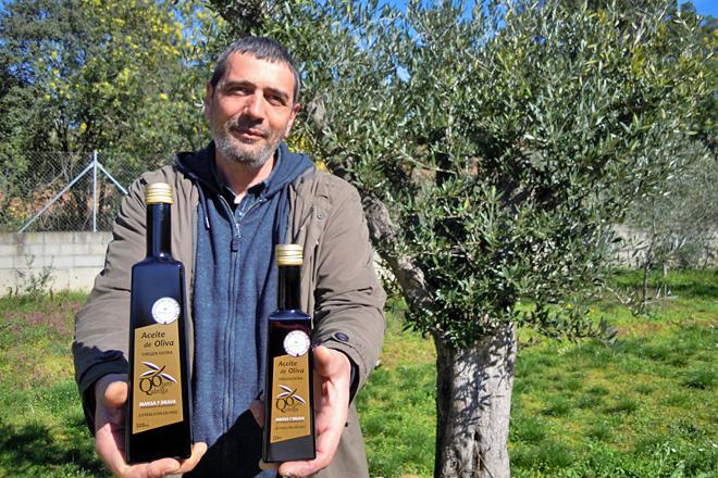 Julio, cos dous formatos que envasan, xunto a unha oliveira plantada na finca onde se atopa a almazara