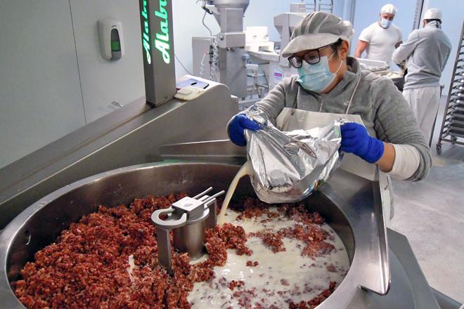 Elena engadindo o leite fresco pasteurizado de Quintián á mestura para facer a masa de croquetas
