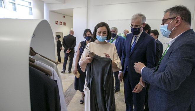 A presidenta executiva de Adolfo Domínguez, Adriana Domínguez, amósalle ó conselleiro de Economía unha prenda elaborada con tencel lyocell.